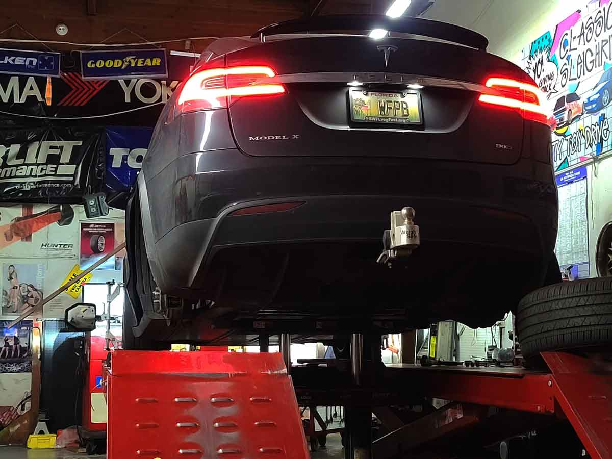 Tesla Model X on wheel alignment rack after installing N2itive acceleration shudder and inner tire wear kit.